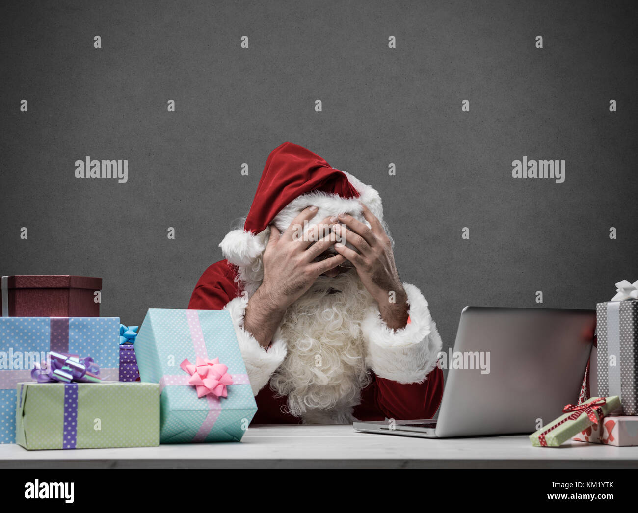 Stressed frustrated Santa Claus with head in hands  connecting with his laptop, he is having computer problems on - Stock Image