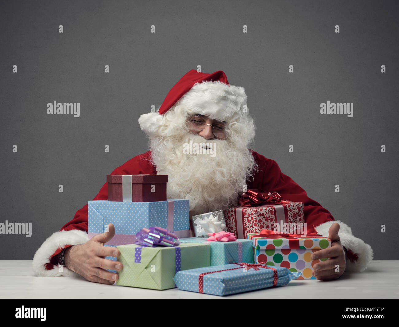 Happy serene Santa Claus holding gifts, Christmas and holidays concept - Stock Image