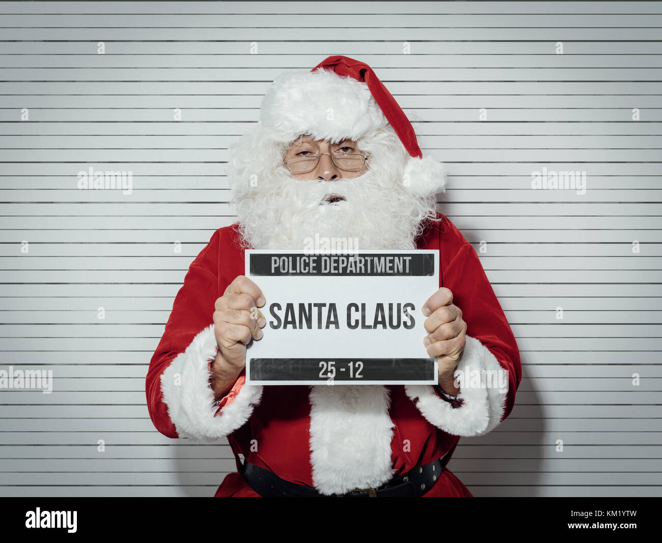 Santa Claus arrested on Christmas eve, he is posing for his mug shot at the police department and holding an identification - Stock Image