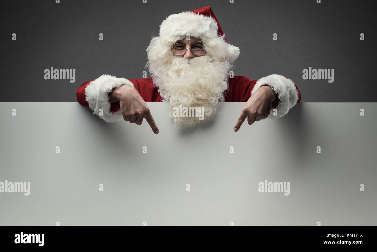 Cheerful Santa Claus pointing at a big blank sign, Christmas and celebrations concept - Stock Image