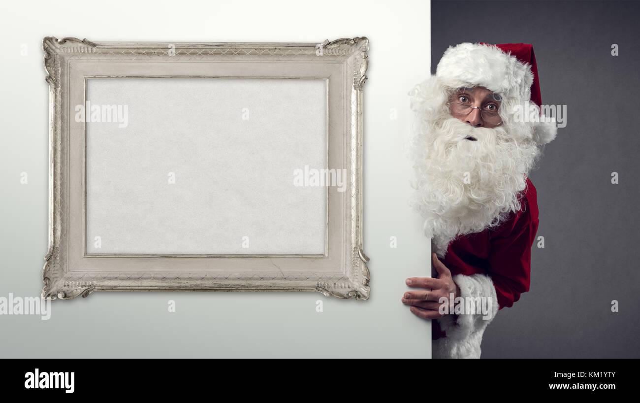 Santa Claus peeking behind a wall and blank decorative frame, Christmas and holidays concept - Stock Image