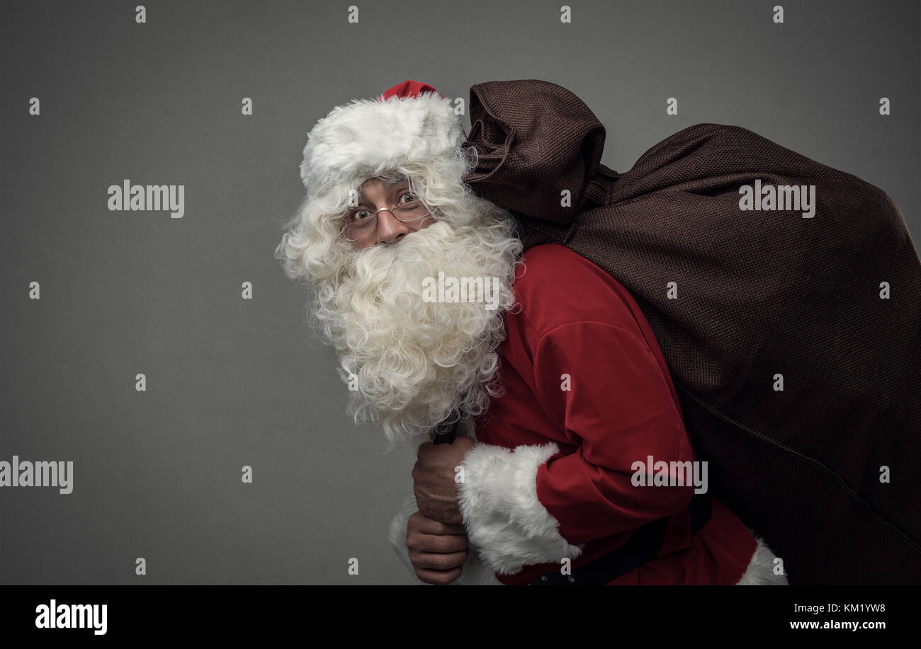 Santa Claus is coming with a sack full of gifts, Christmas and holidays concept - Stock Image