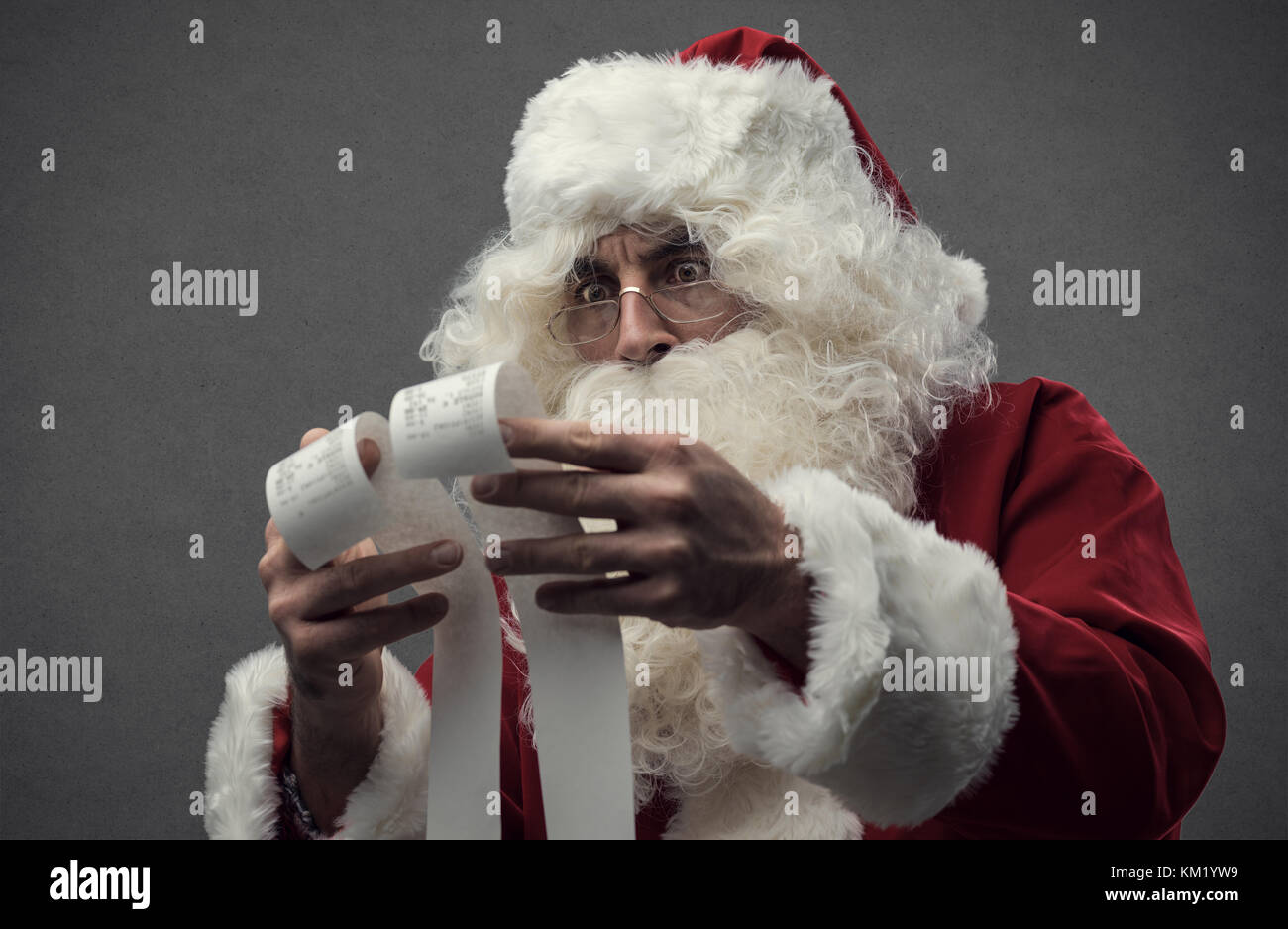 Astonished shocked Santa Claus checking Christmas's shopping expensive bills, he is holding two long receipts - Stock Image