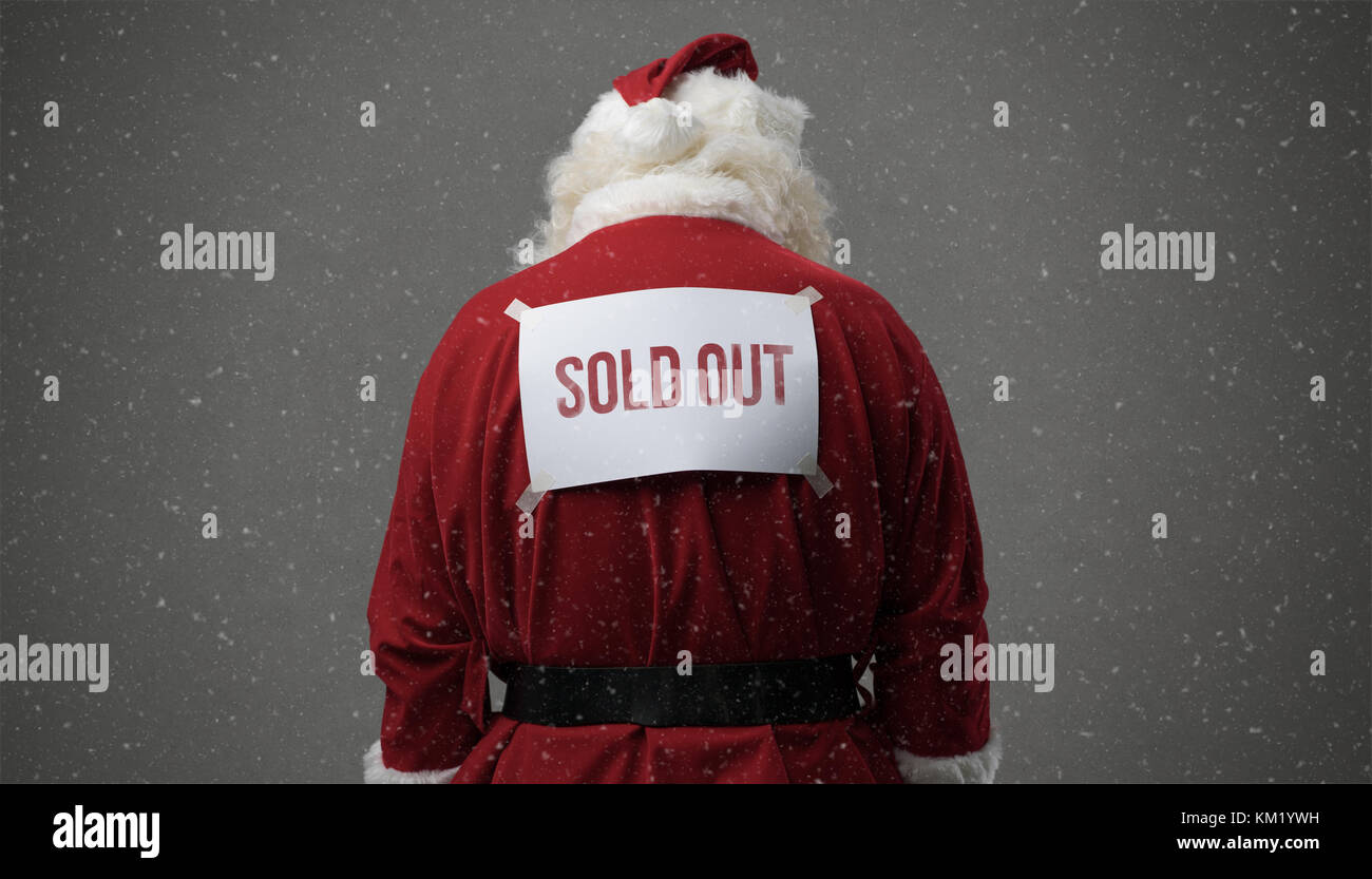 Santa Claus with sold out sign on his back and snow falling - Stock Image