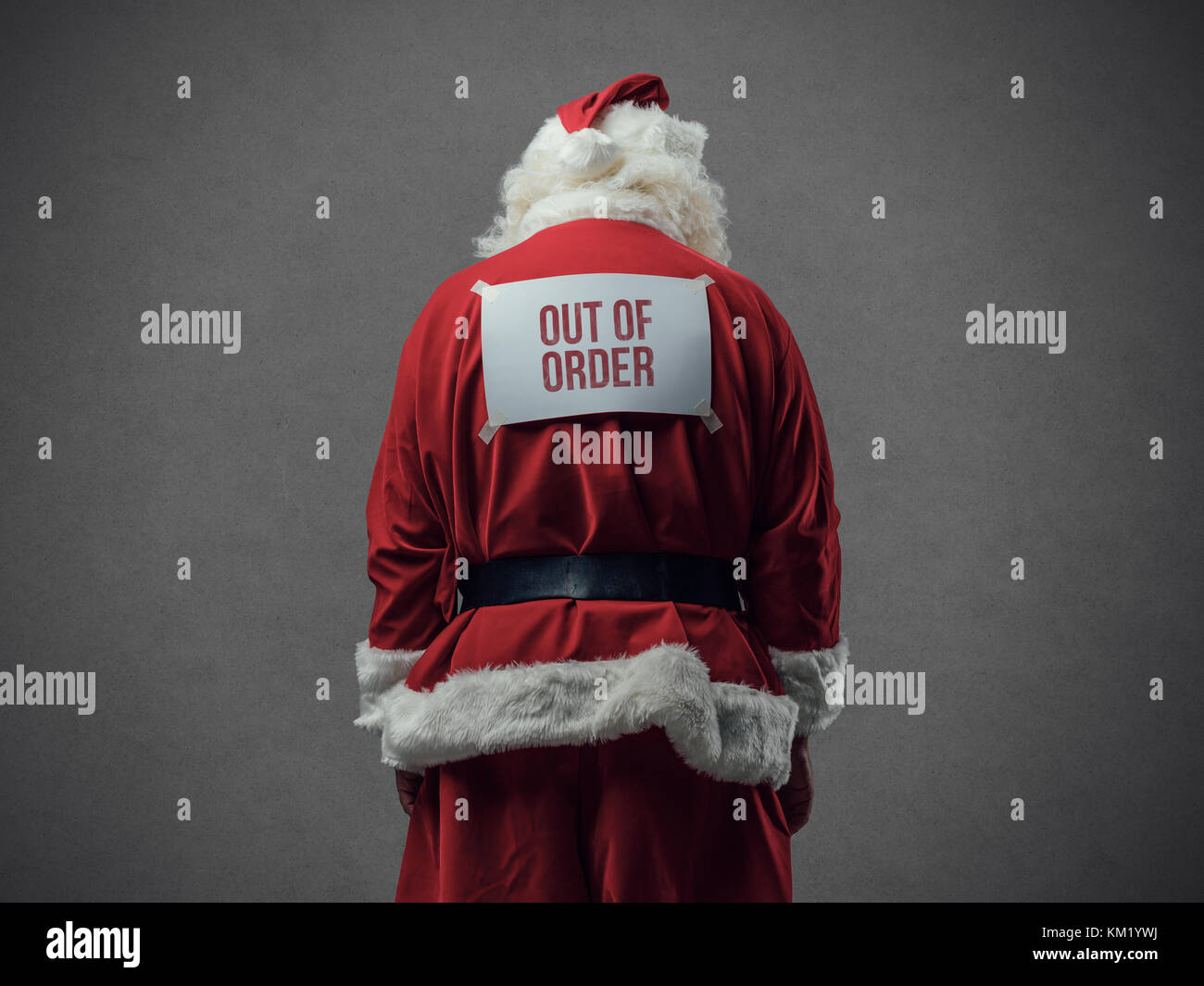 Santa Claus with out of order sign on his back, he is looking down, back view - Stock Image