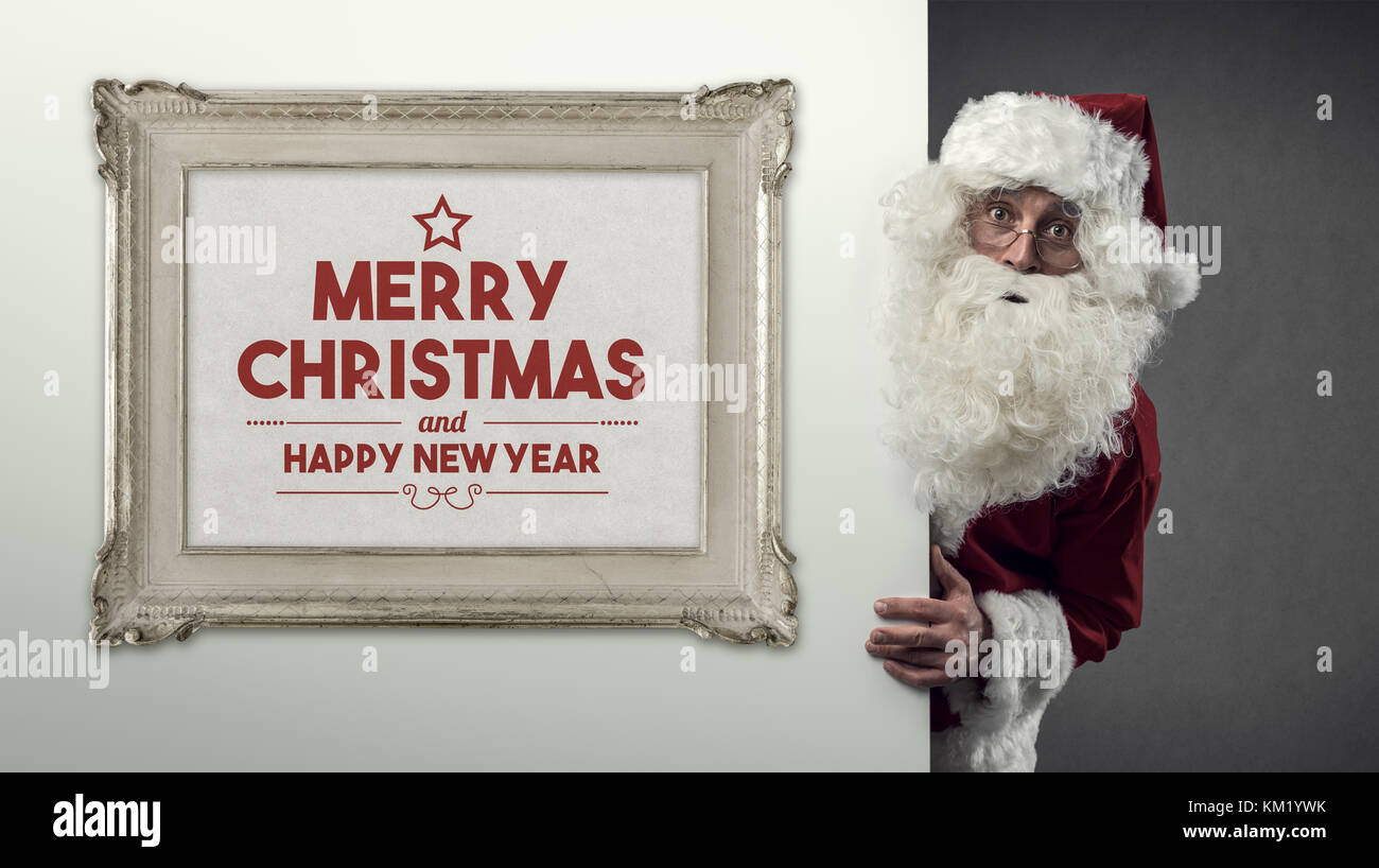Santa Claus peeking behind a wall and decorative frame with Christmas wishes, celebrations and holidays concept - Stock Image