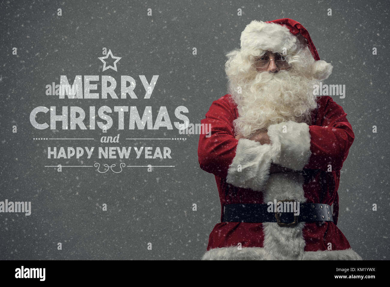Confident Santa Claus posing with arms crossed and Christmas wishes, snow falling on the background - Stock Image