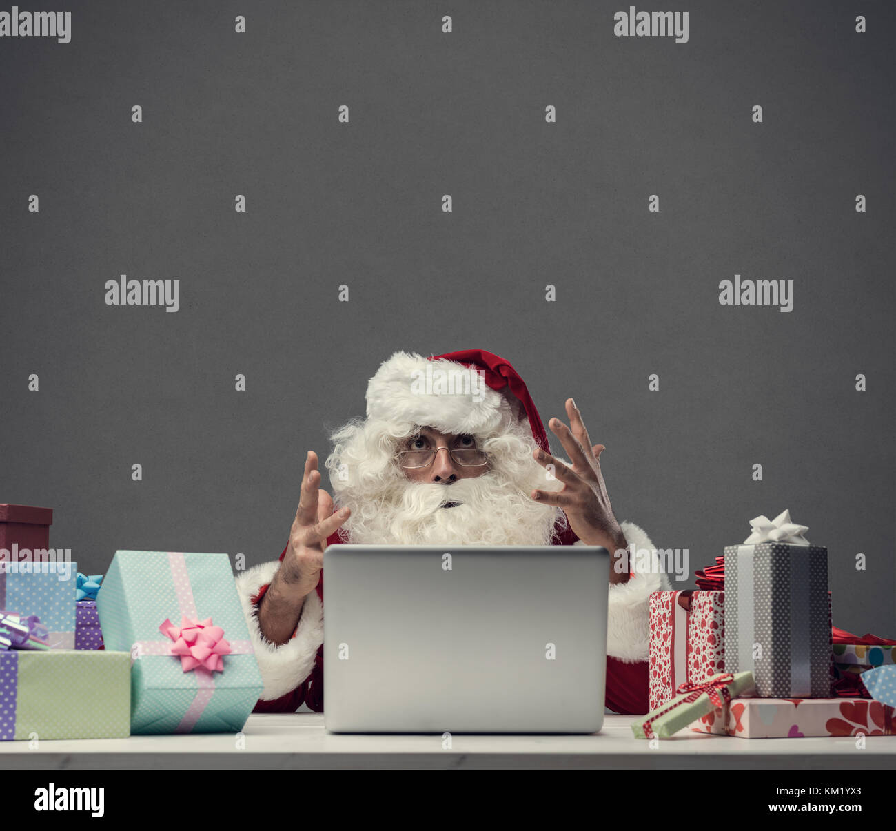 Angry frustrated Santa Claus yelling at the laptop on Christmas Eve: computer and connection problems - Stock Image