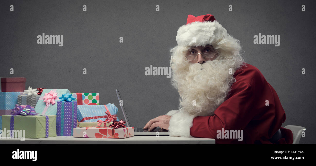 Santa Claus connecting and working online with his laptop, he is preparing gifts and shopping online on Christmas - Stock Image