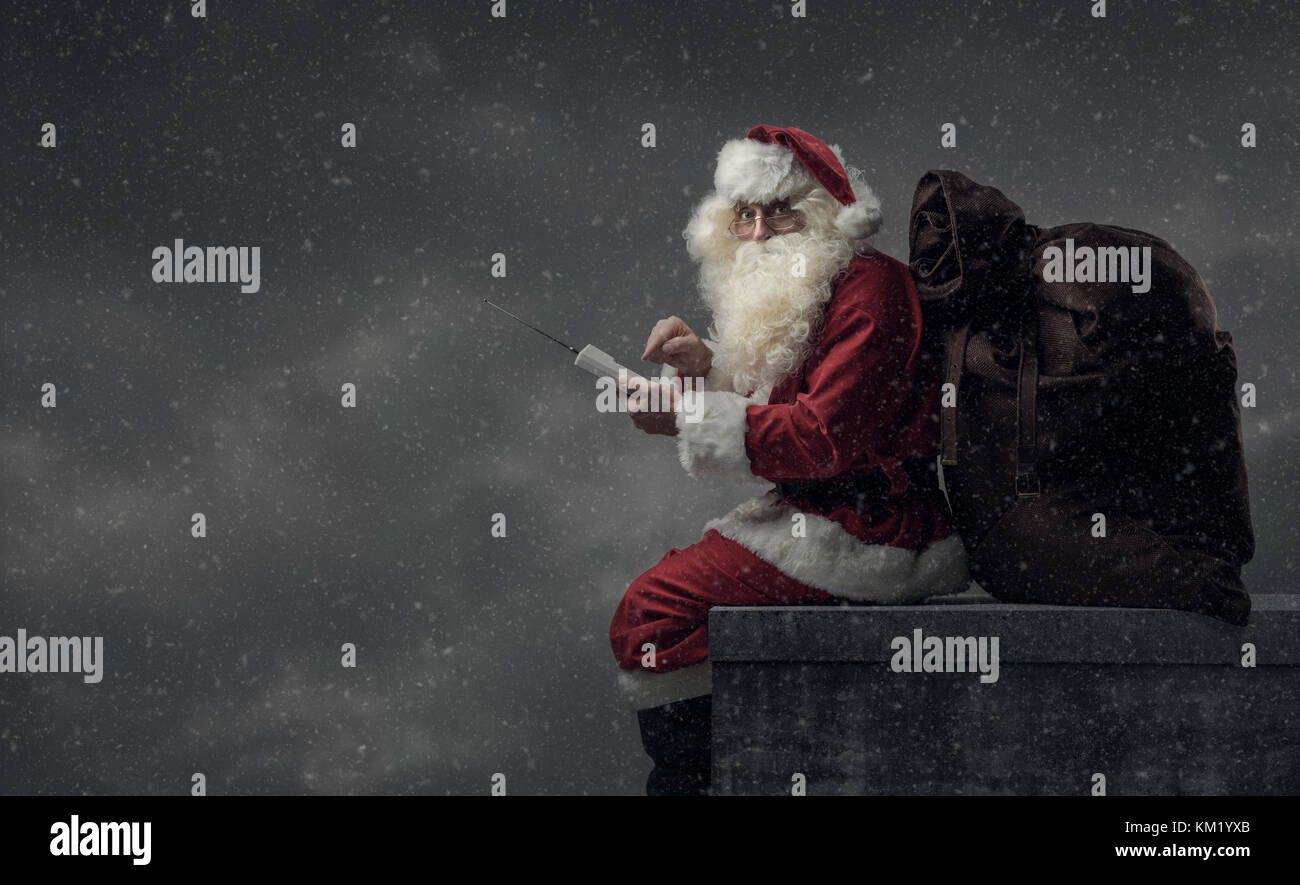Santa Claus bringing gifts on Christmas Eve: he is calling with a phone and sitting on the roof with a big sack - Stock Image