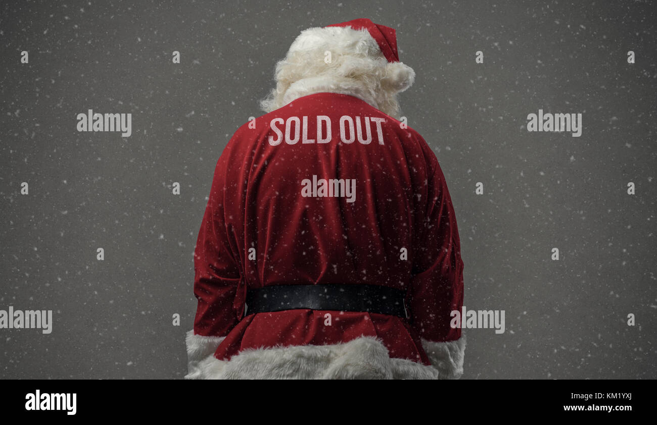 Santa Claus with sold out text on his back and snow falling - Stock Image