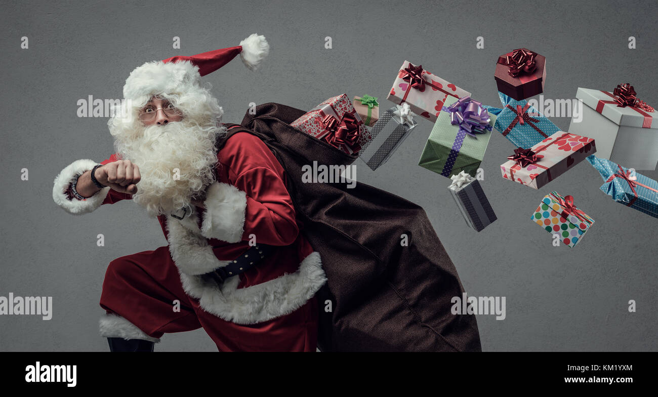 Funny Santa Claus running and delivering Christmas presents, he is checking time and losing gifts from his sack - Stock Image