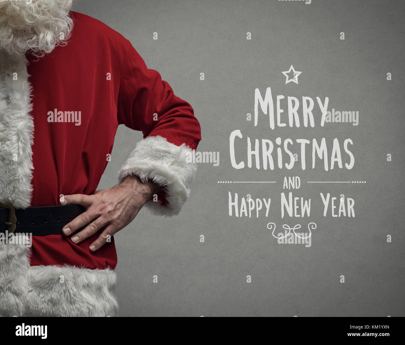 Confident Santa Claus posing with arms akimbo close up and Christmas wishes - Stock Image