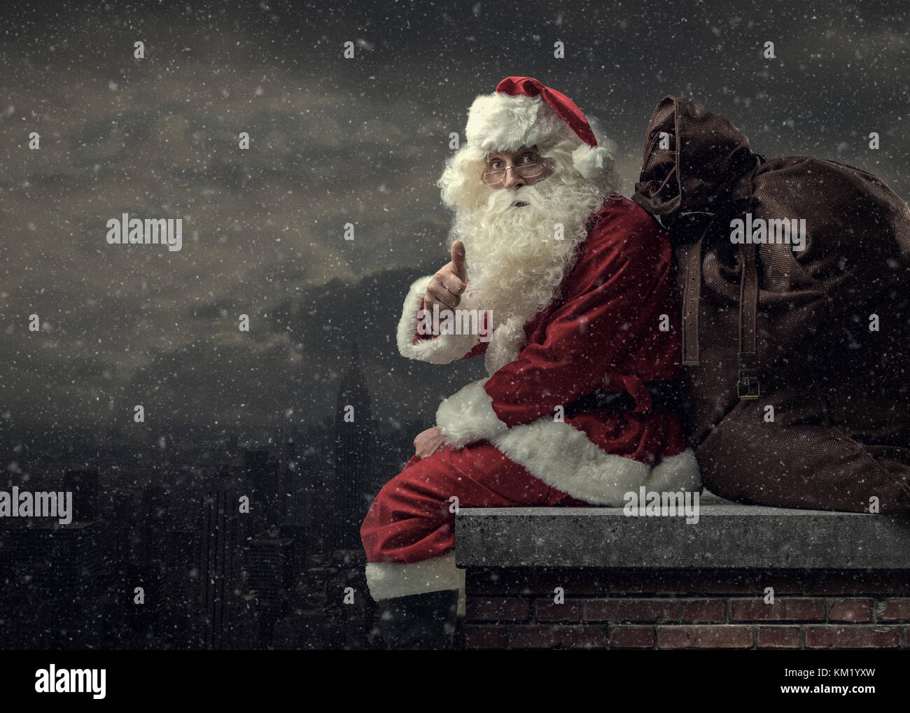 Happy Santa Claus bringing gifts on Christmas Eve: he is sitting on a roof, carrying a big sack and giving a thumbs - Stock Image