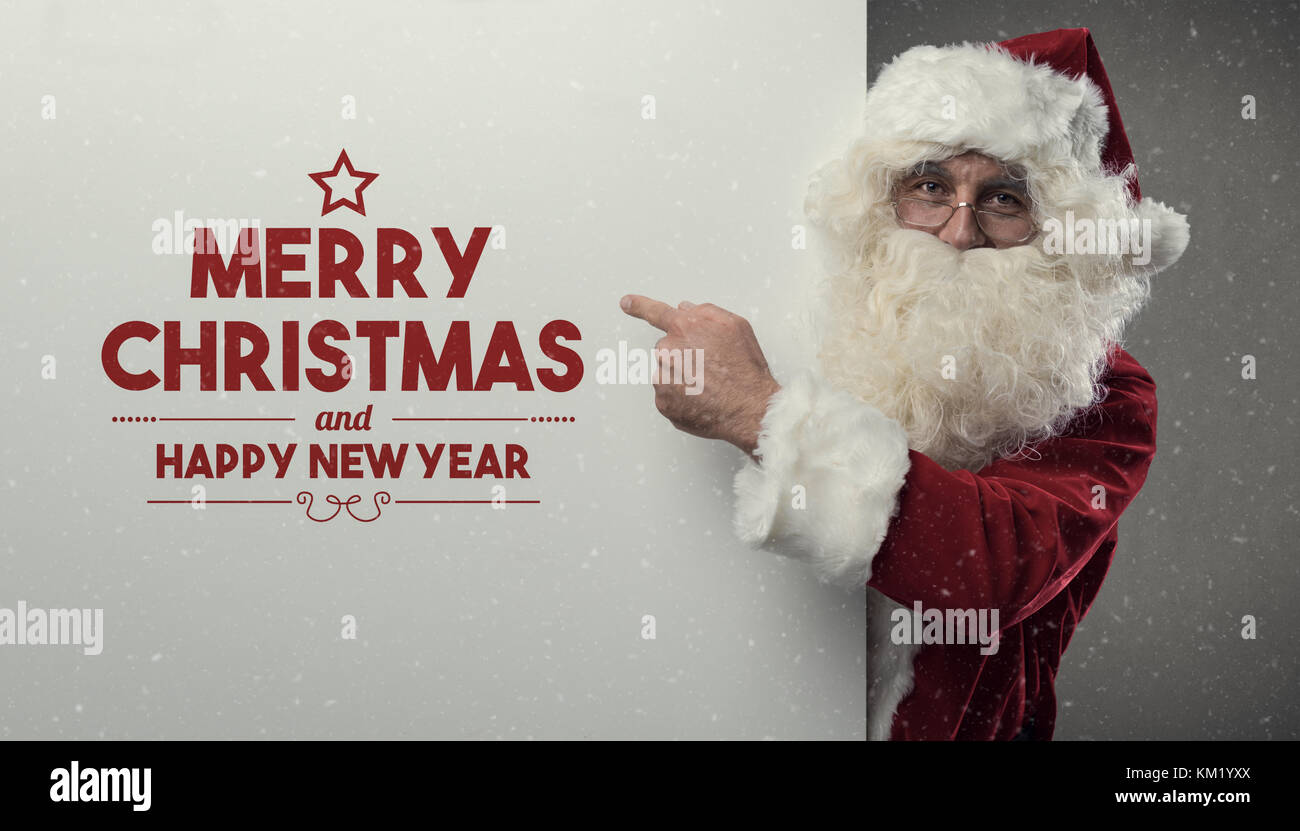 Happy Santa Claus wishing you a Merry Christmas and a Happy New Year, he is pointing and looking at camera - Stock Image
