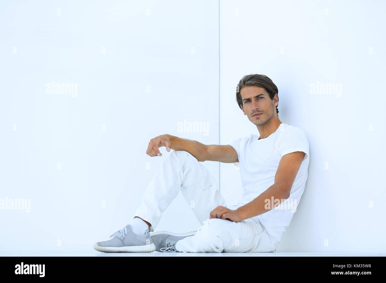 sad young man sitting beside a white wall - Stock Image