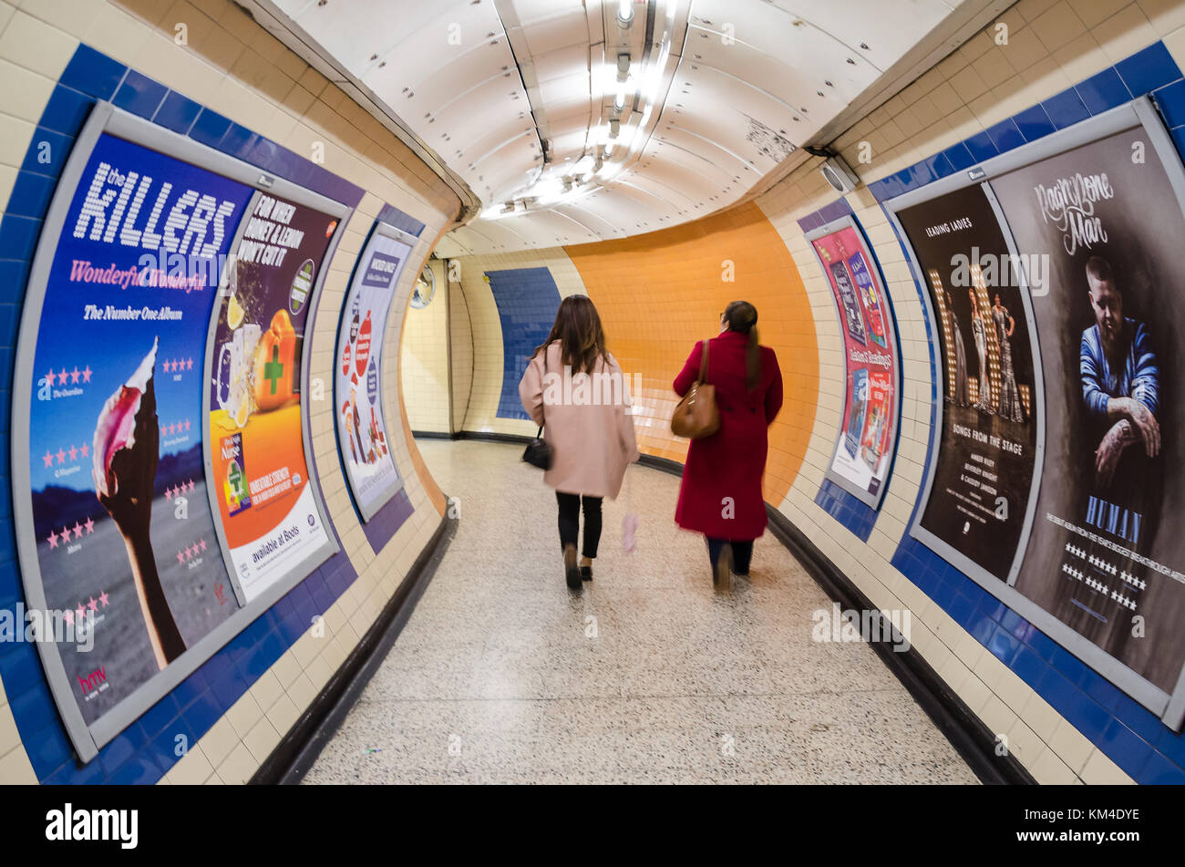 Two ladies walk through a connecting tunnel on the London Underground. The walls are covered with advertising posters. - Stock Image