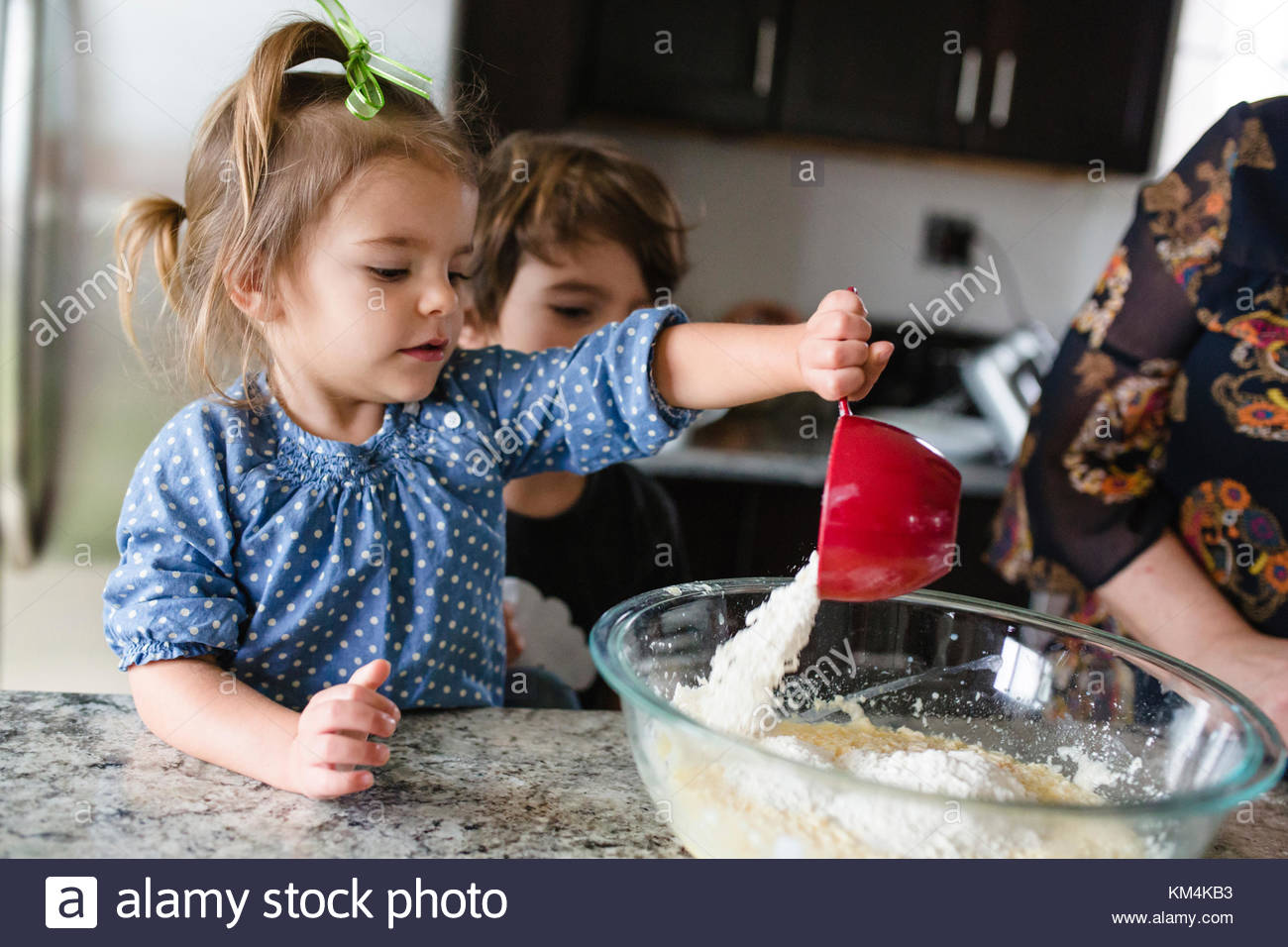 Young girl with green ribbon in her hair standing in a kitchen, pouring flour into glass mixing bowl, young boy - Stock Image