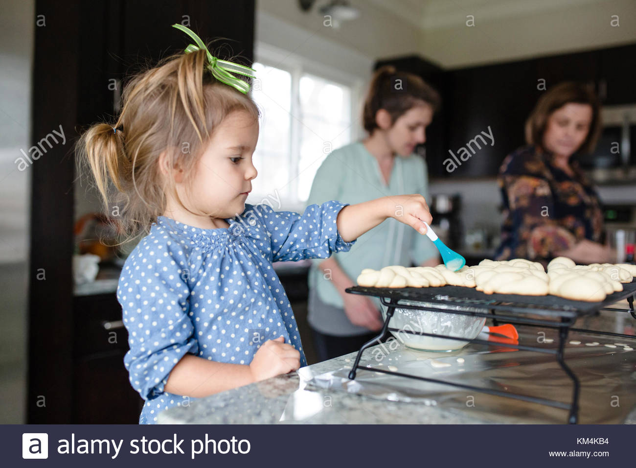 Young girl with green ribbon in her hair standing in a kitchen, holding a spoon, decorating cookies, two women in - Stock Image