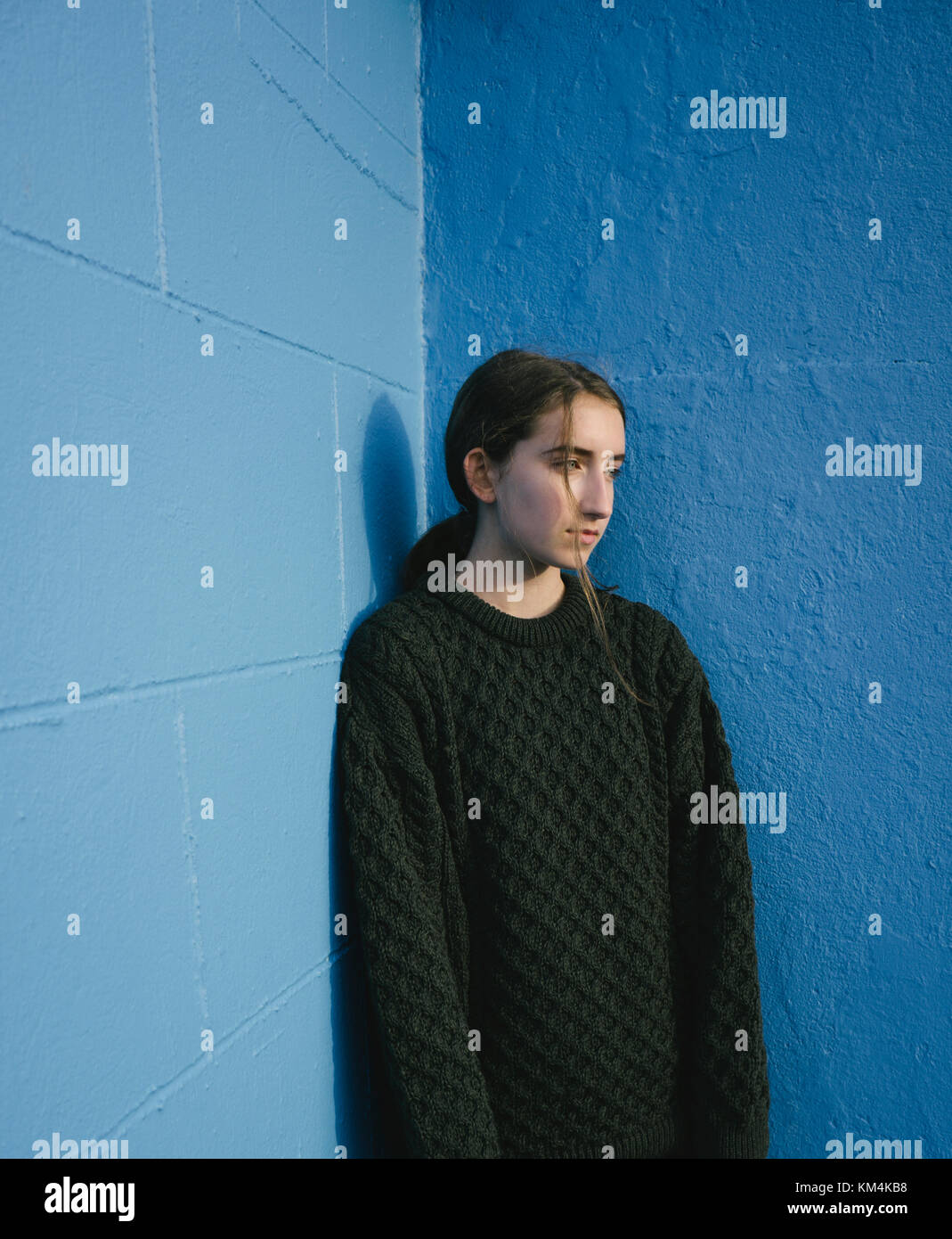 Portrait of teenage girl with brown hair in ponytail wearing black knitted jumper, leaning against blue wall. - Stock Image