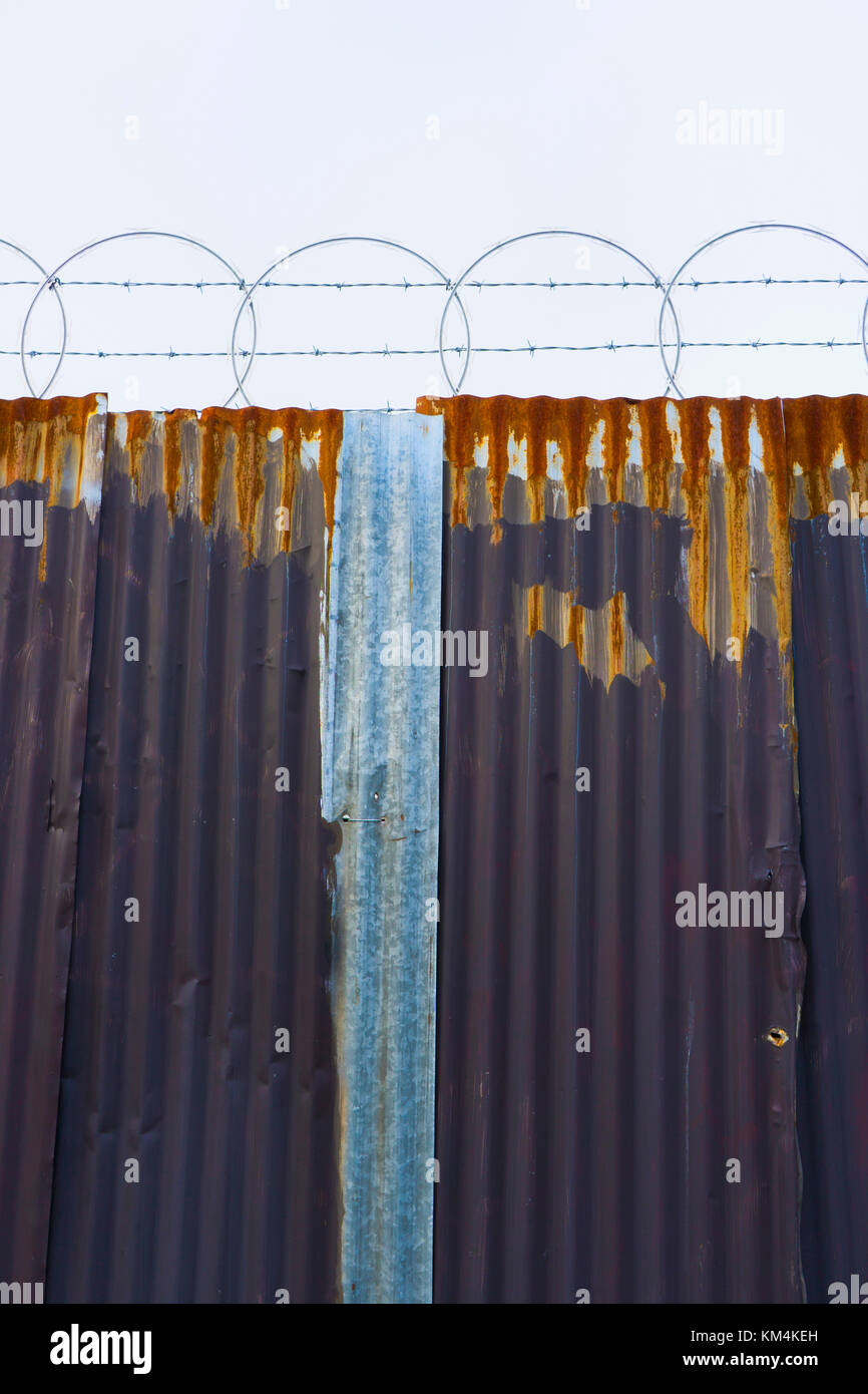 Worn corrugated metal fence, razor wire above. - Stock Image