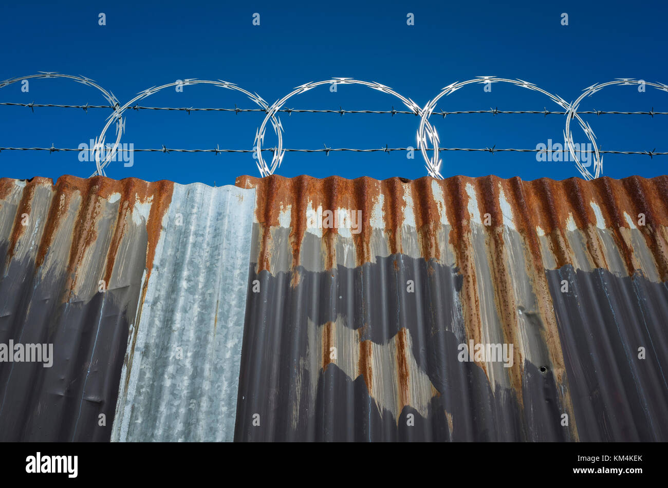 Low angle view of worn corrugated metal fence, razor wire above. - Stock Image