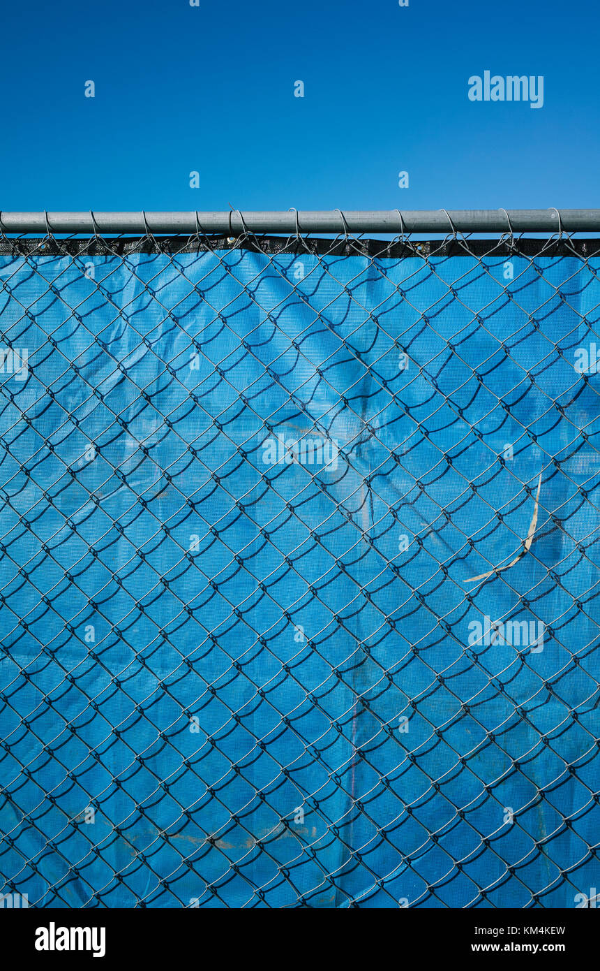 Blue fabric behind chainlink fence, blue sky above. - Stock Image