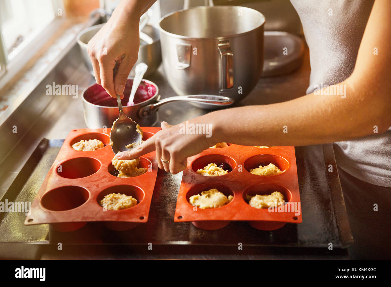 High angle close up person using spoon to place small portions of cake dough into silicone mold. - Stock Image