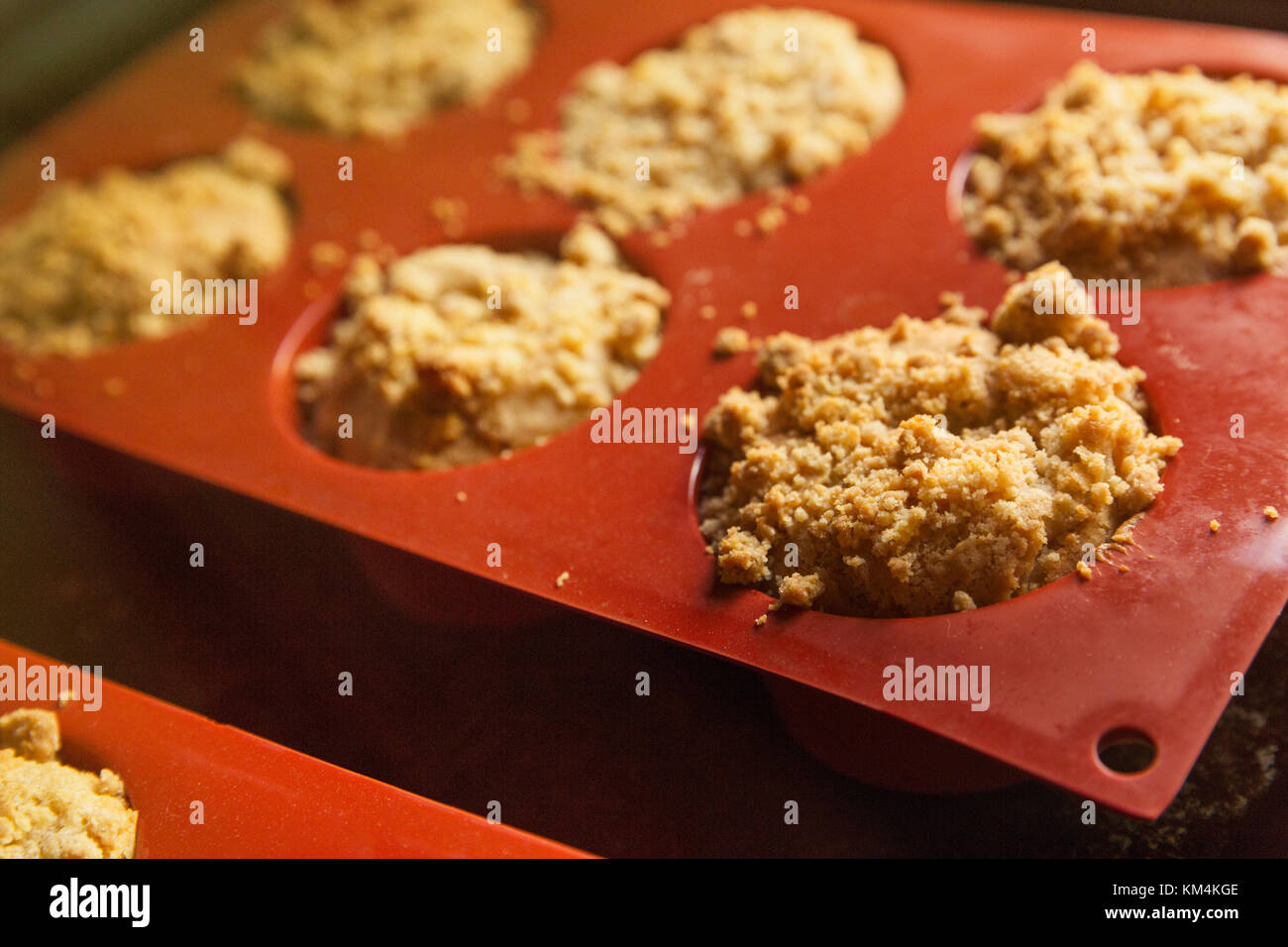 High angle close up of freshly baked small cakes in silicone mold. - Stock Image