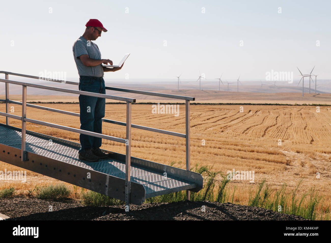A wind farm technician standing and using a laptop at the base of a turbine on a wind farm in open countryside at - Stock Image