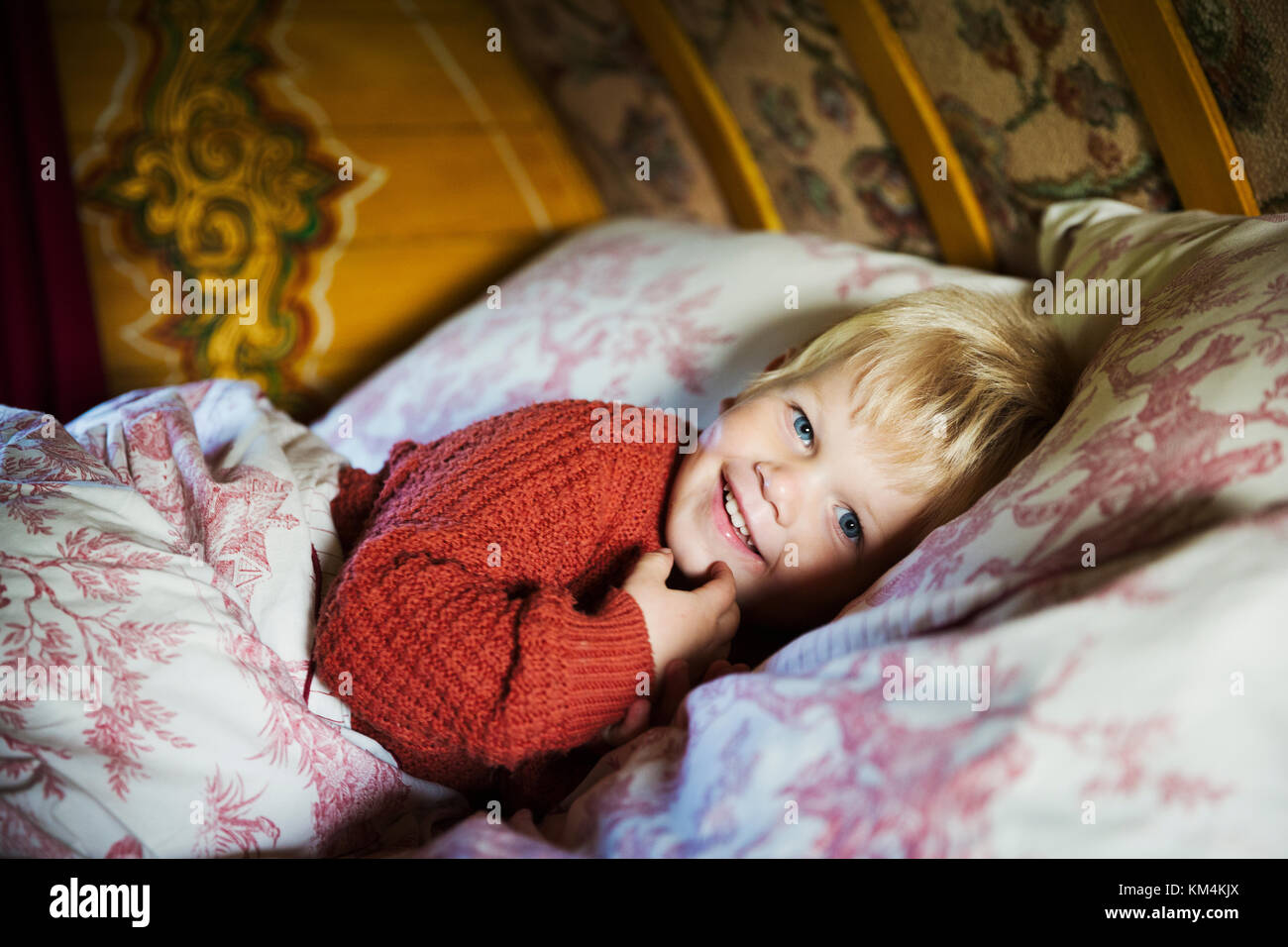 A boy lying in bed under a curved bow top roof of a gypsy caravan, looking at the camera. - Stock Image
