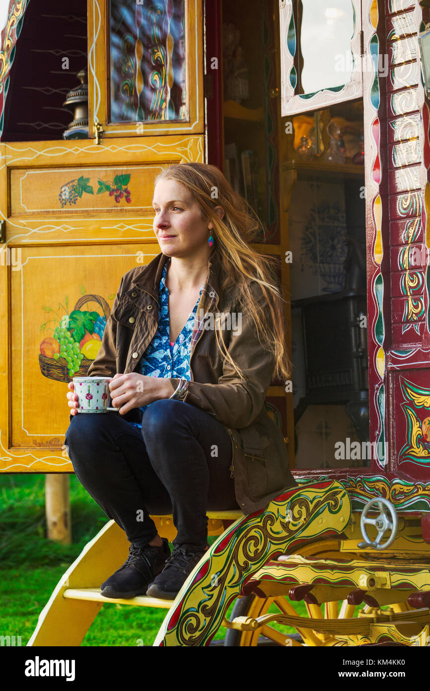 A woman seated on the steps of a caravan, holding a mug of tea. - Stock Image