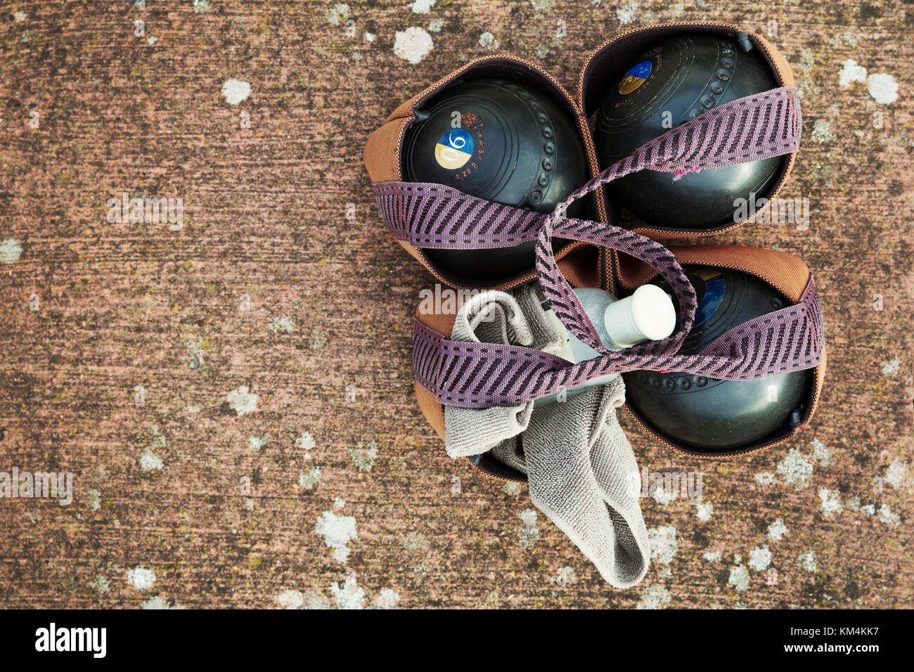 Overhead view of four wooden lawn bowls in a ball carrier with a cloth to clean them. - Stock Image