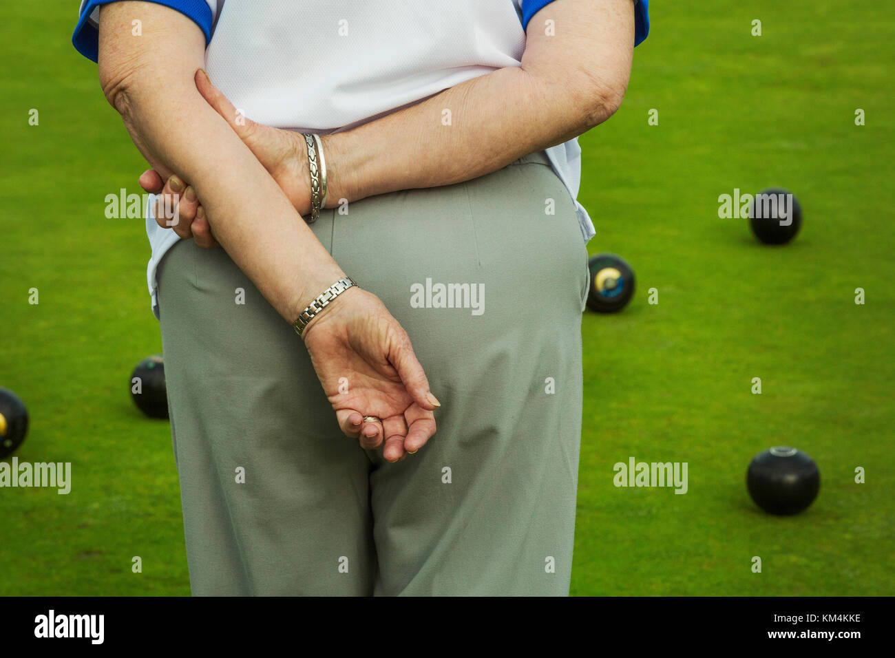 Rear view of a woman lawn bowls player with hands behind her back, and lawn bowls ranged across the playing surface. - Stock Image