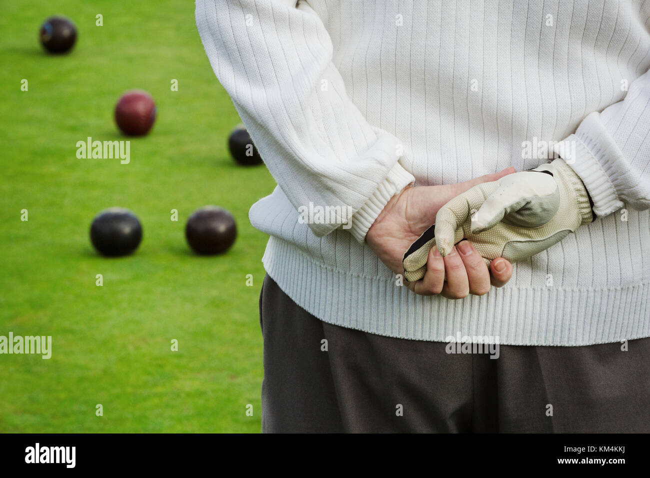 Rear view, a man standing with his hands clasped behind him, one hand in a playing glove, at a lawn bowls match, - Stock Image