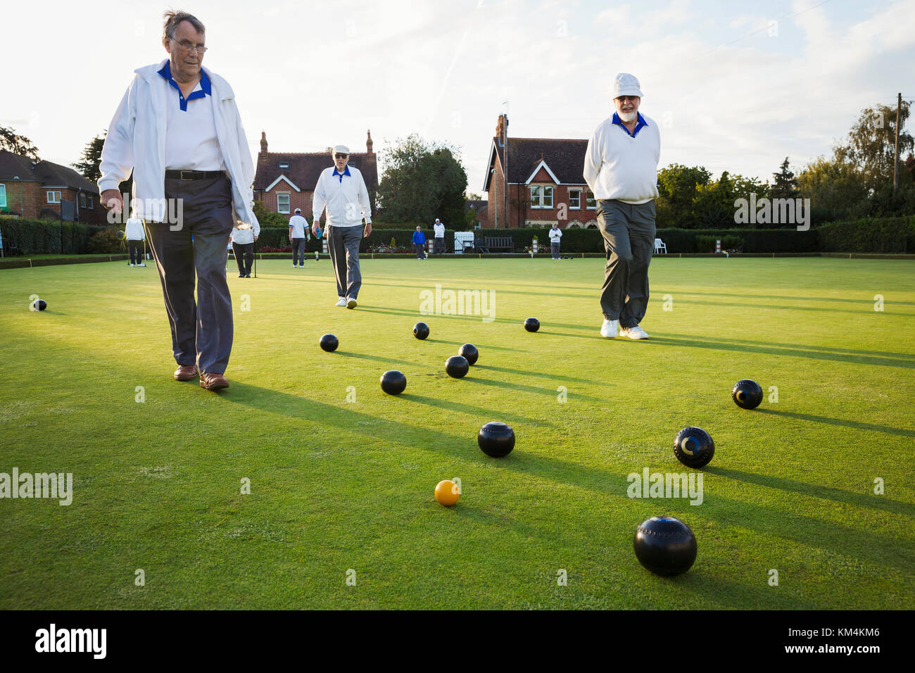 Three lawn bowls players, men walking across the green, the playing surface, at an end with bowls clustered around - Stock Image