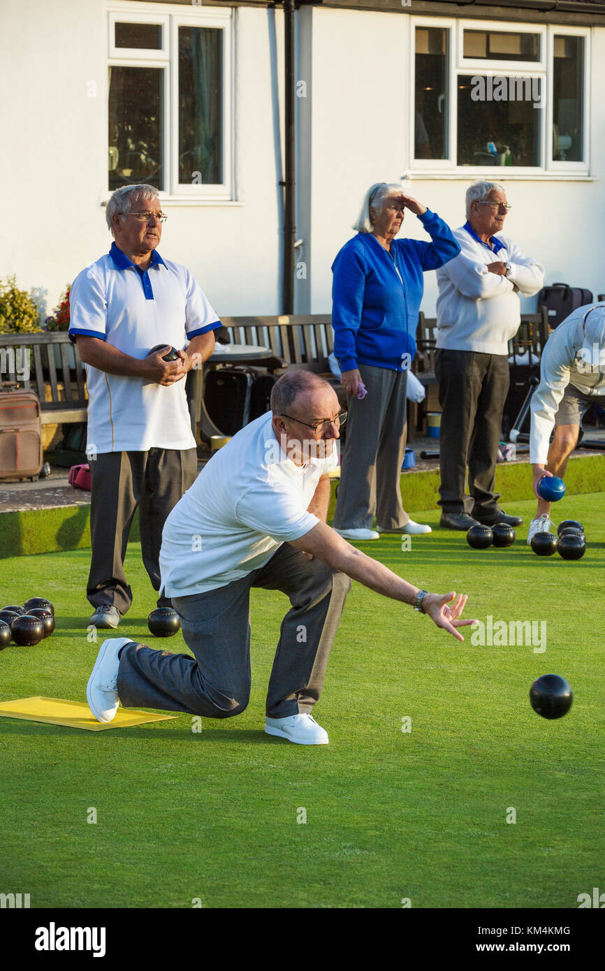 Four people at a lawn bowls match or game. One man kneeling and delivering a bowls shot, and three people in the - Stock Image