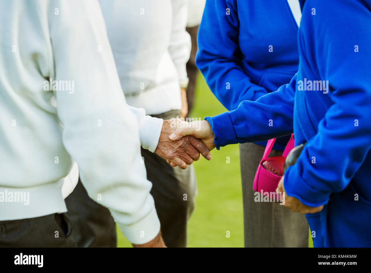 Two teams, four people shaking hands before or after a sporting match. - Stock Image