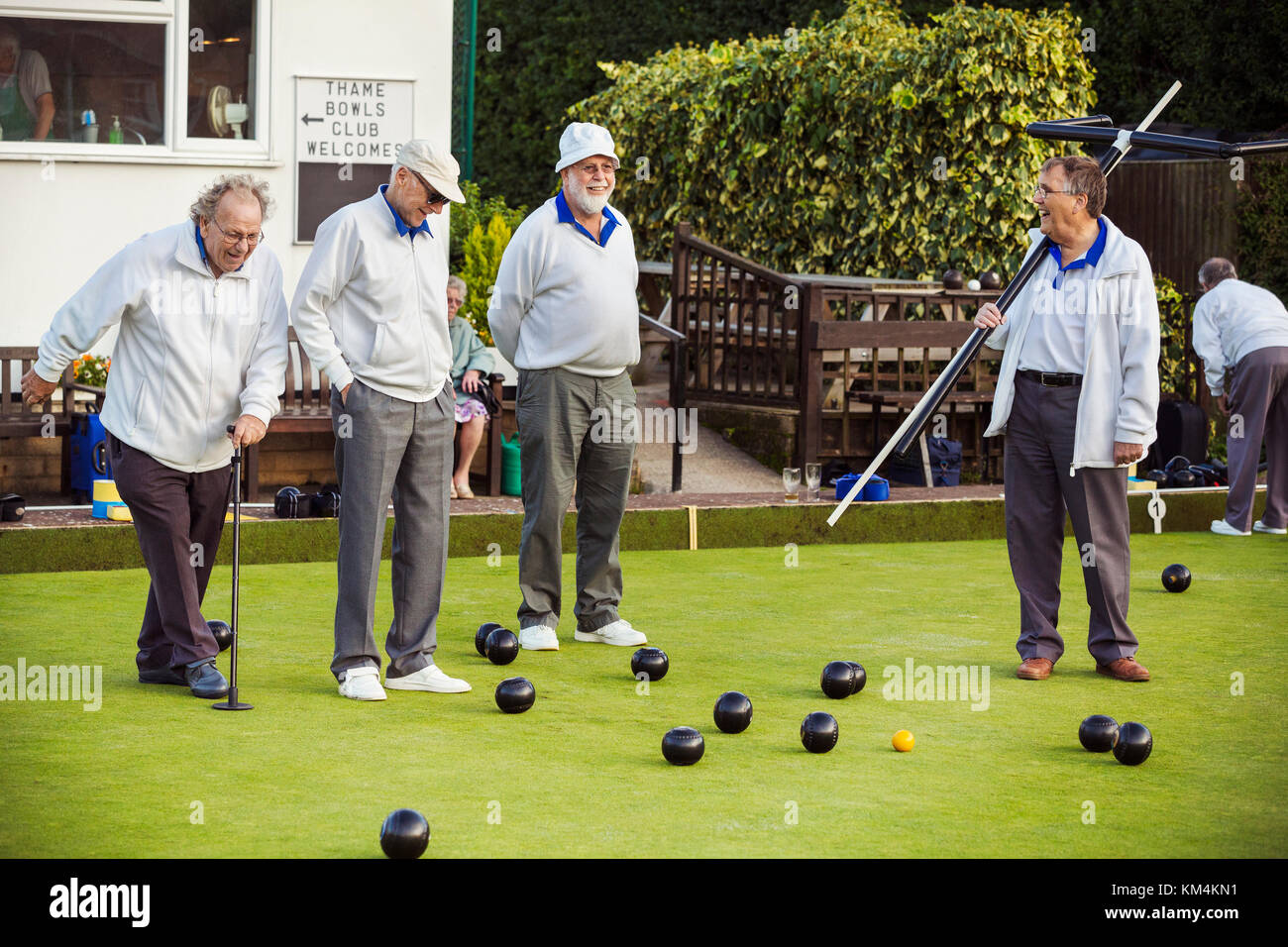 Four men on the lawn bowls green, one wearing an umpire's coat, at an end. - Stock Image
