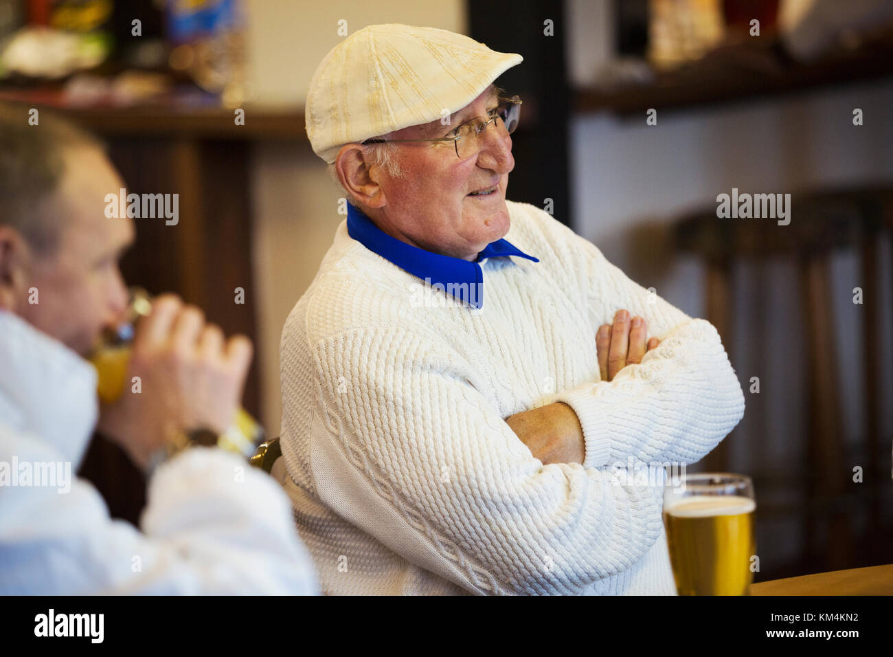 Two men at a lawn bowls club seated with pints of beer. Post match analysis. - Stock Image