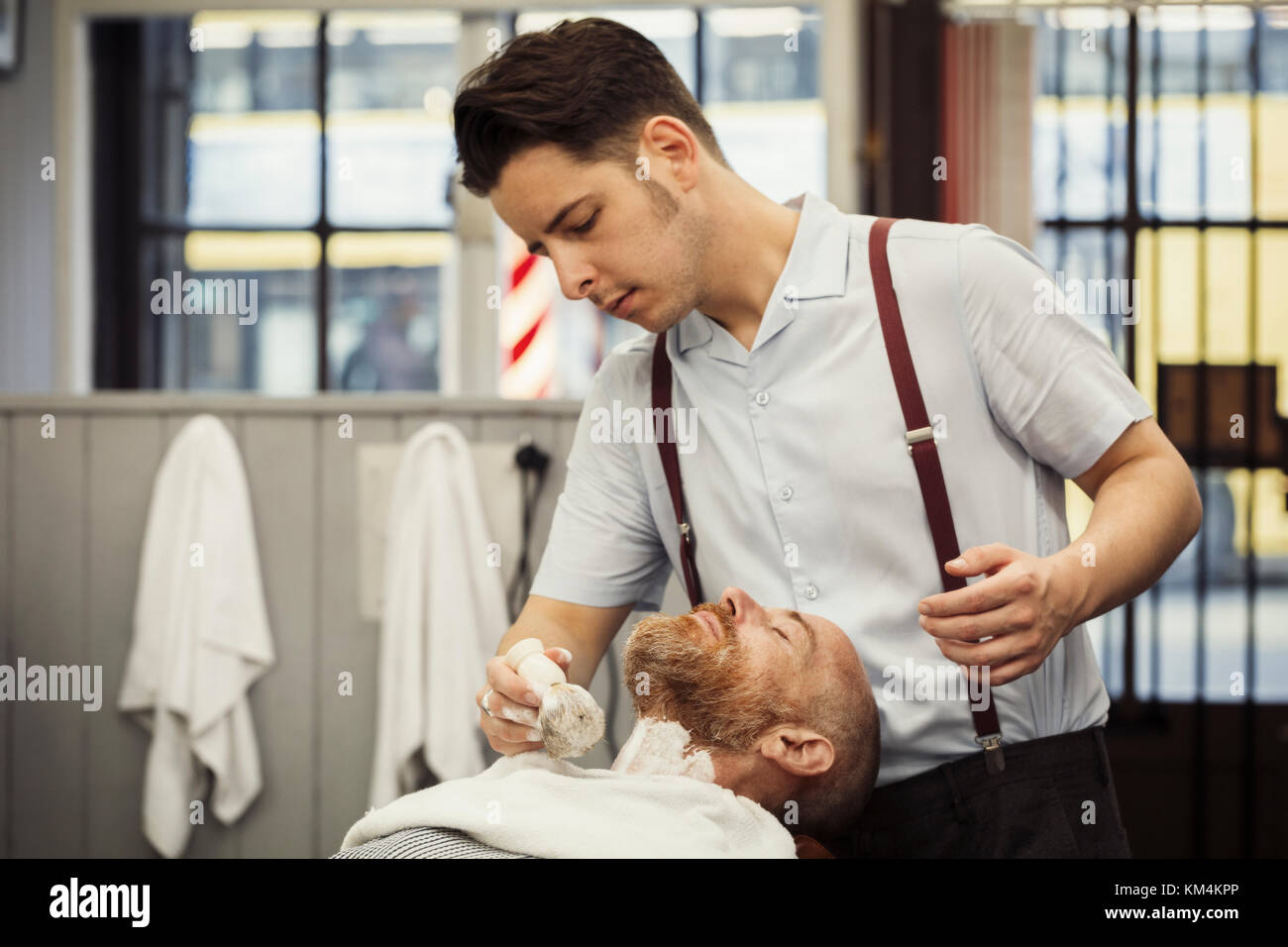 A customer sitting in the barber's chair, having a wet shave. A man using a shaving brush to lather his chin - Stock Image