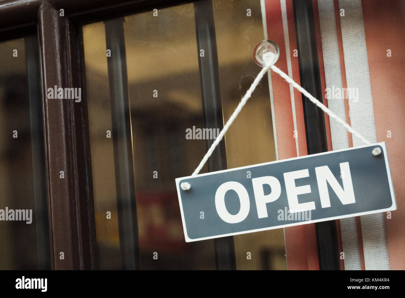 A shop door with a sign saying Open. - Stock Image