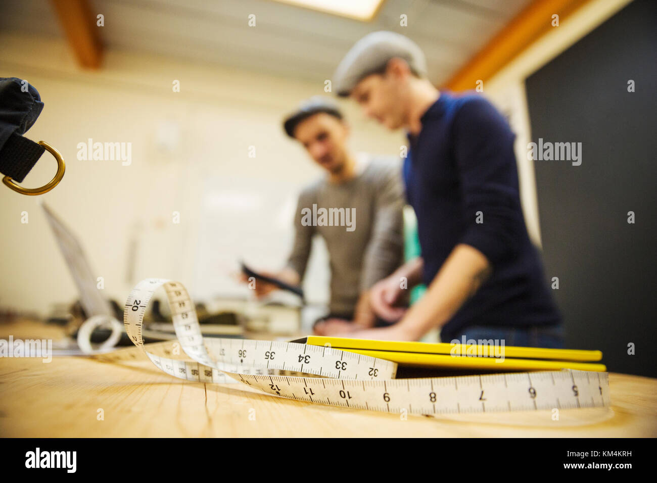 Two men at a workbench, using a digital tablet and laptop, a measuring tape in the foreground. - Stock Image