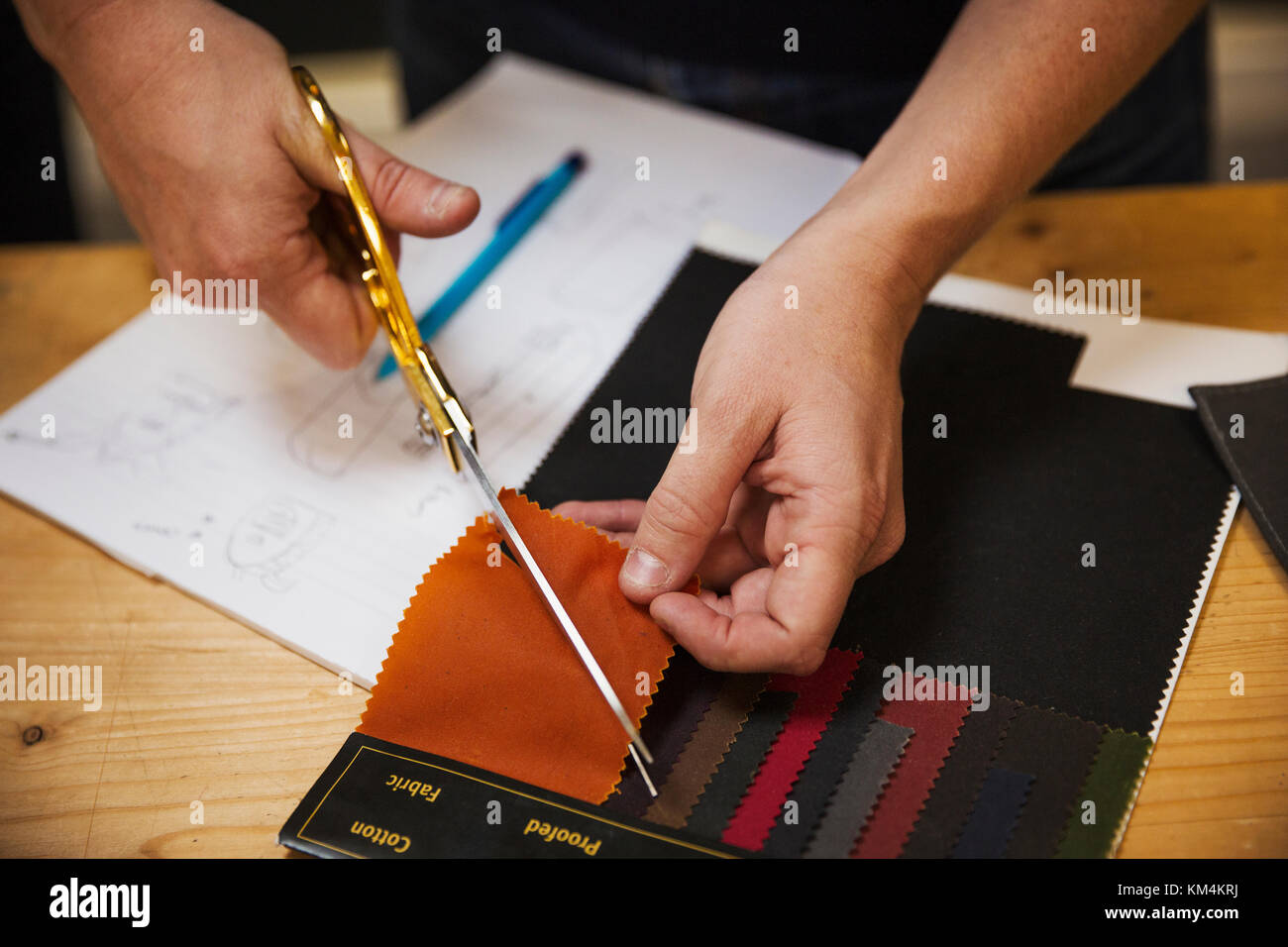 A person using shears to cut a fabric sample at a workbench, overhead view. - Stock Image