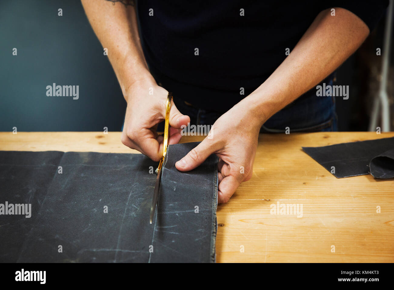 A man cutting a piece of grey fabric with shears. - Stock Image
