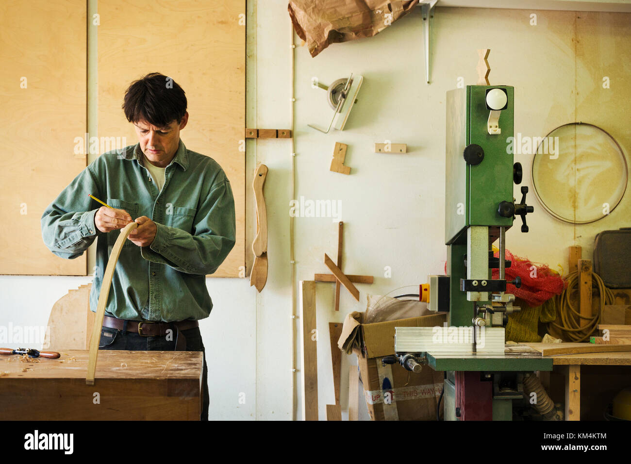 A craftsman marking a piece of curved wood with a pencil. - Stock Image