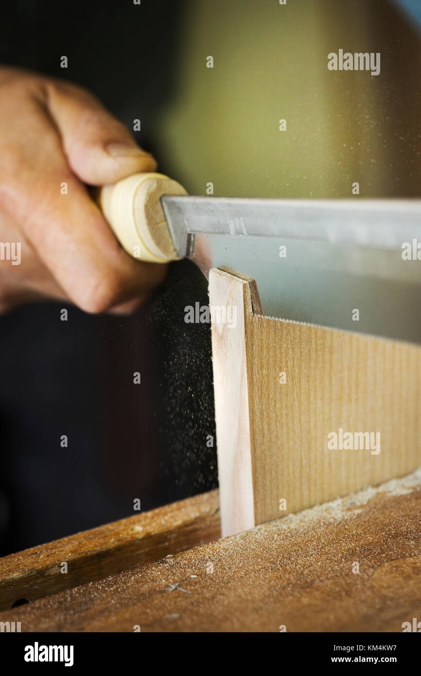 A craftrsman using a hand saw to make a small cut in the end of a piece of wood. - Stock Image