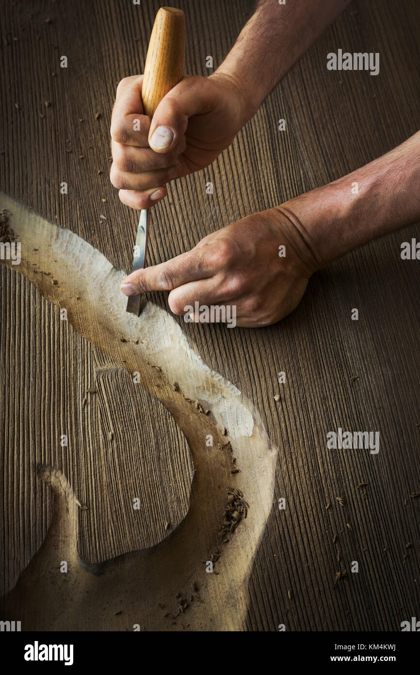 A craftsman using a chisel to carve out a deep groove in a piece of wood. - Stock Image
