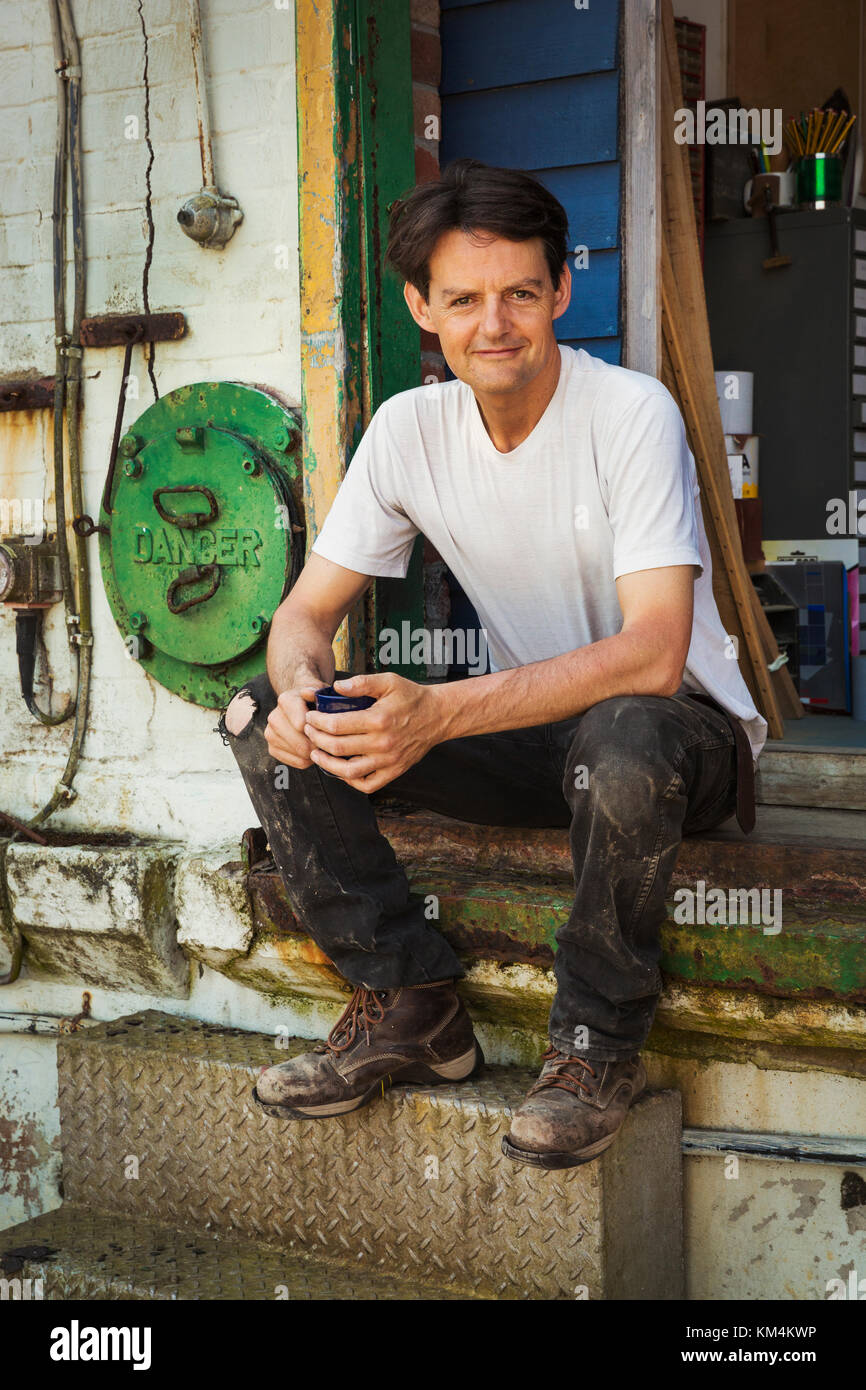 A man in a teeshirt having a tea break, sitting on the steps of a workshop. - Stock Image