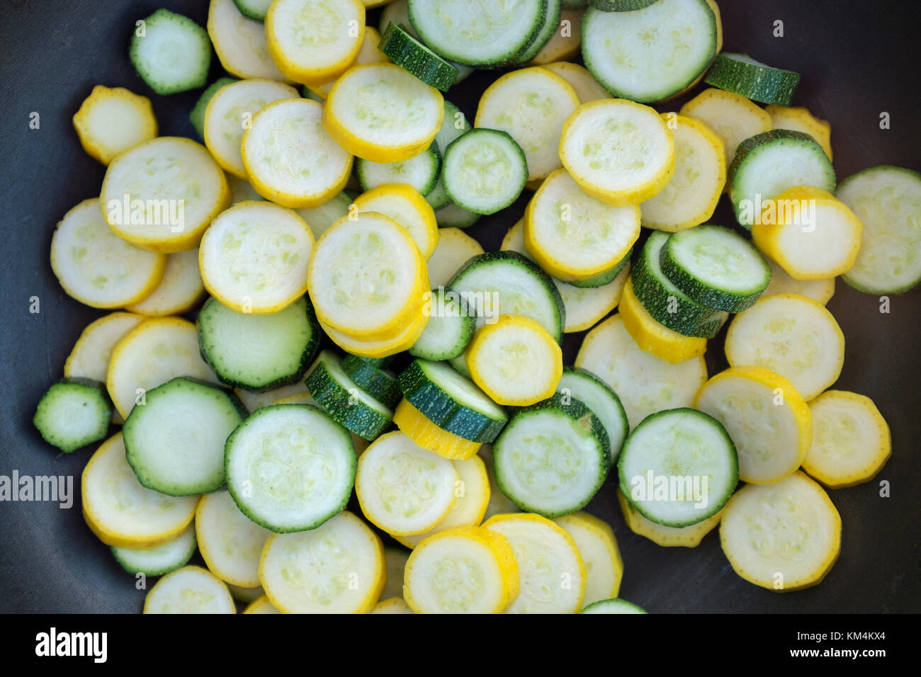 Sliced fresh zucchini courgette vegetables with green and yellow skins in a frying pan. - Stock Image